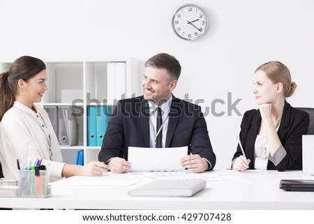 Positive businesspeople sitting beside desk in light office