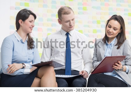 Positive businesspeople working togther, sitting in light office