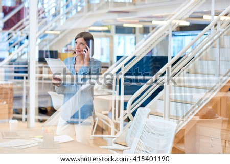 Positive businesswoman on her phone in a modern creative office  - stock photo