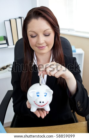 Positive businesswoman putting money into a piggybank sitting in her office - stock photo