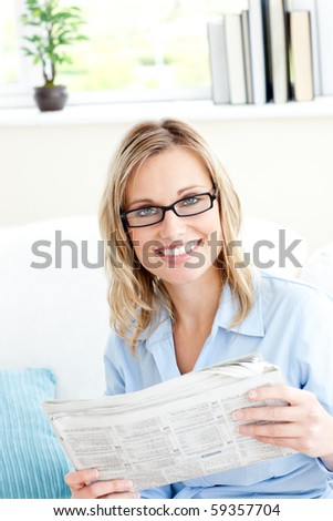 Positive businesswoman reading newspaper in the office on the sofa - stock photo