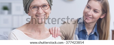 Positive cancer woman with headscarf and girl holding hand on her shoulder, panorama.
