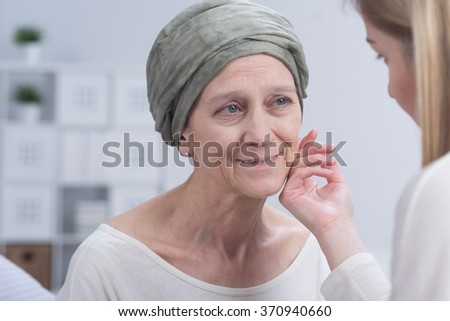 Positive cancer woman with headscarf and young girl touching her face - stock photo