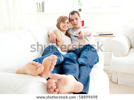 Positive caucasian couple lying together on the couch watching television at home