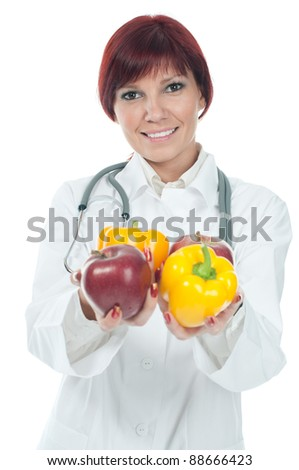 Positive caucasian female doctor holding fresh fruits and vegetables, over a white background - stock photo