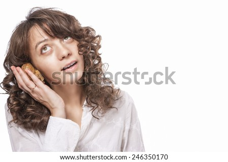 Positive Caucasian Female with Long Curly Hair Listening to Sea Shell. Surprised Facial Expression. Isolated Over Pure White Background.Horizonal Image Composition - stock photo