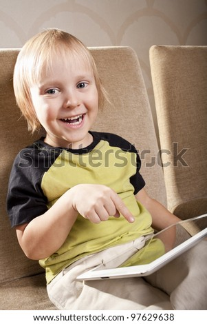 positive caucasian small boy  is with tablet computer at home