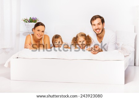 Positive cheerful family laying on white bed - stock photo