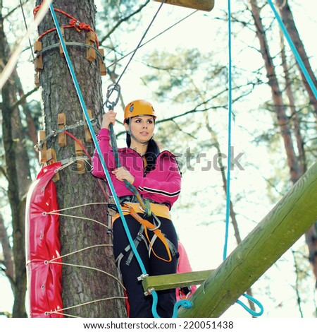 positive cheerful girl having fun doing tree climbing. Beautiful girl in the outfit climbing climbs over obstacles between trees