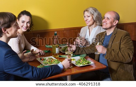 Positive cheerful middle class people enjoying food and wine in cafe - stock photo