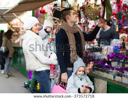 Positive cheerful young family of four at Christmas market - stock photo