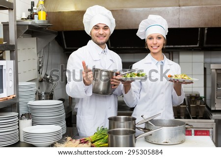 Positive chef and his assistant preparing meal in cafe - stock photo