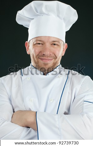 Positive chef in uniform with his arms crossed smiling and looking at camera - stock photo