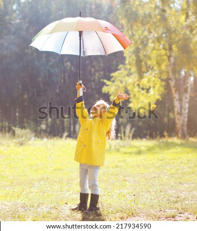 Positive child with colorful umbrella having fun in autumn day - stock photo