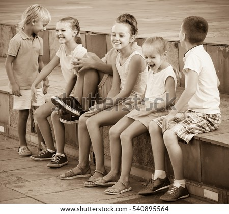 positive children in school age playing charades outdoors