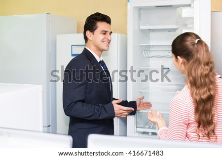 Positive couple buying domestic refrigerator in supermarket