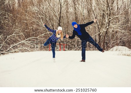 Positive couple playing in the snow park - stock photo