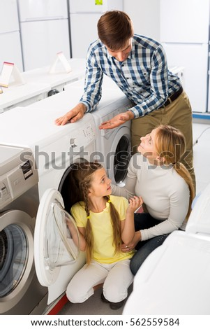 Positive couple with girl buying washing machine in hypermarket