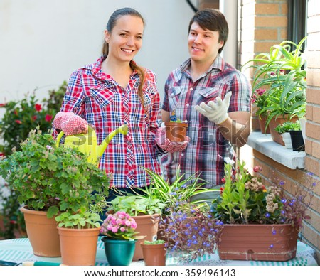 Positive couple working with flowers at the balcony. Focus on girl