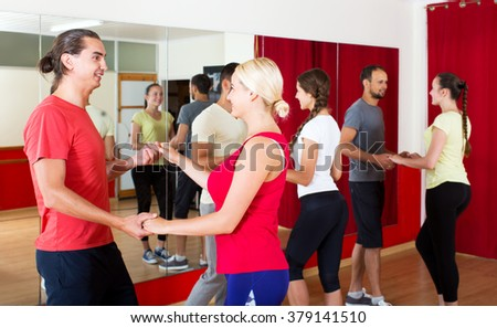 positive couples dancing Latino dance in class