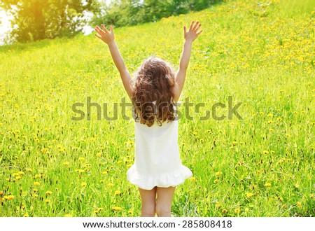 Positive curly little girl enjoying summer sunny day, having fun, happy child walking in summer  - stock photo