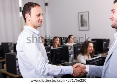 Positive customer service manager shaking hand of employee - stock photo