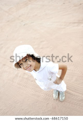 Positive cute boy with a cap standing on sahara sand, tourist, large copy-space