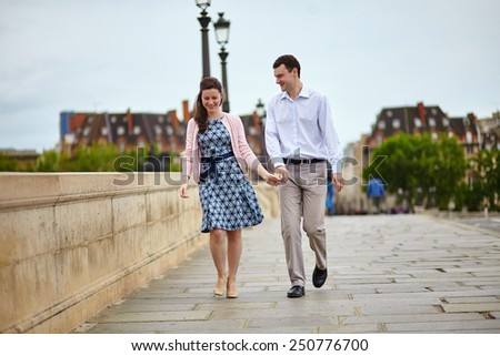 Positive dating couple in Paris walking hand in hand - stock photo