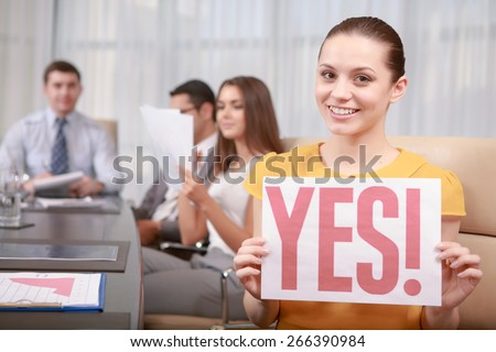 Positive decision. Cheerful attractive female manager happily holding a paper with text YES at the business meeting - stock photo