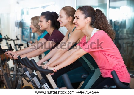 Positive  elderly and young women working out hard in sport club