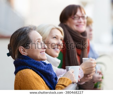 Positive elderly woman in warm clothes having cup of hot tea on terrace. Focus on brunette woman