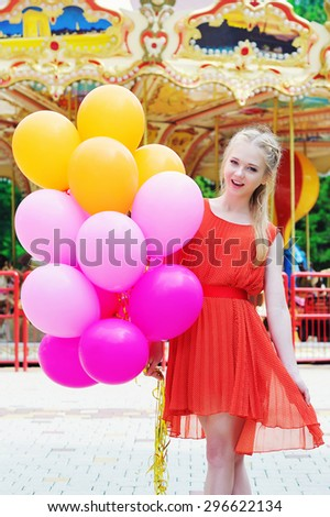 Positive emotions concept, cheerful young woman holding colorful latex balloons in the amusement park in front of the carousel - stock photo