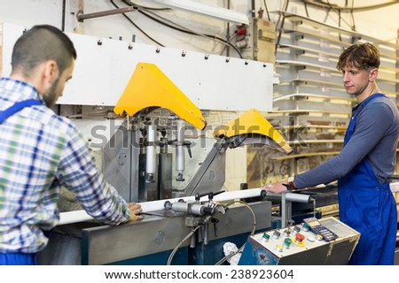 positive employes working on a machine in factory - stock photo