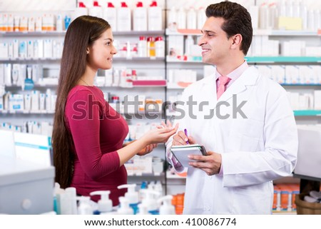 Positive experienced pharmacist counseling female customer