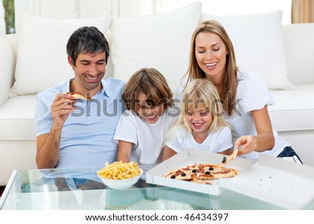 Positive family eating pizzas sitting on sofa