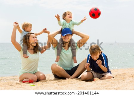 Positive family of five playing at sea beach and resting together - stock photo