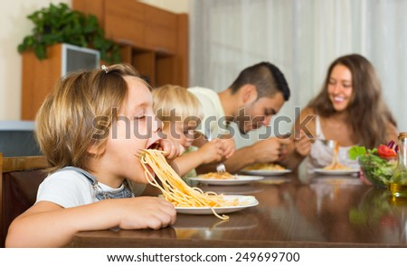 Positive family of four having lunch with spaghetti at home - stock photo
