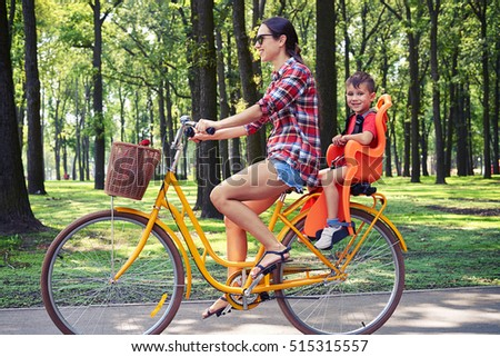 Positive family of mother and her son riding a bike together on a bright sunny day in the park
