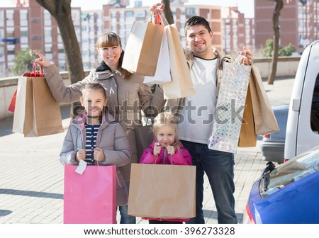 Positive family portrait with many purchases in bags at parking lot