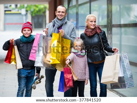 Positive family with two joyful school age children with many purchases in shopping tour  - stock photo