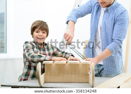Positive father and son doing renovation  - stock photo