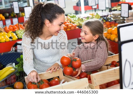 Positive female and little girl shopping globe tomatoes in grocery