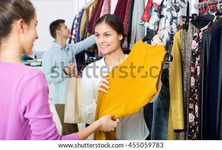 Positive female assistant serving customer asking in clothing boutique