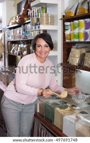 Positive female customer selecting various groats in the store with ecological goods