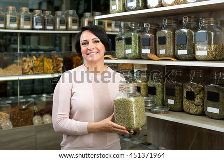 Positive female customer selecting various herbs in the store with ecological goods