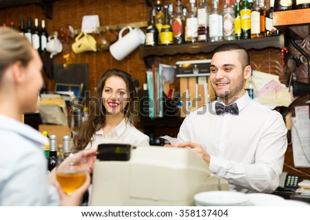 Positive female drinking wine at counter and chatting with bartenders indoors