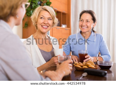 Positive female pensioners drinking tea at the table at home. Focus on brunette - stock photo