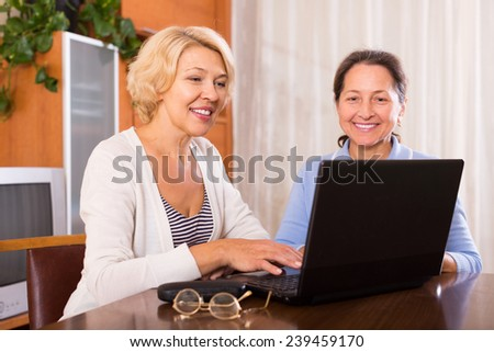 Positive female pensioners sitting with laptop indoor. Focus on blonde  - stock photo