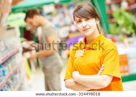 Positive female seller or shop assistant portrait  in hardware supermarket store - stock photo