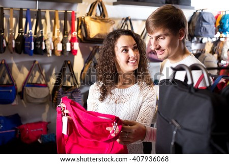 Positive female shopgirl helping young man to select handbag in store - stock photo